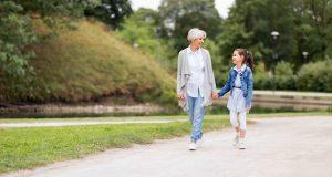 Grandmother and granddaughter walking at park